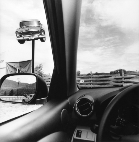 Picture by Lee Friedlander from inside his car of a car on an advertizing pole